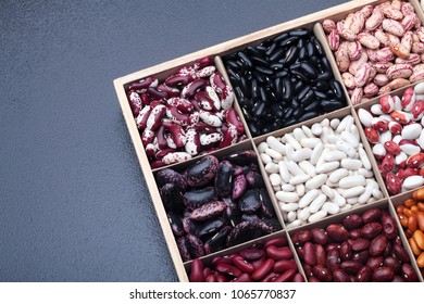 Different types of legumes beans. In wooden box.Varieties of beans.Top view.Closeup.Texture.Copy space.On dark stone background