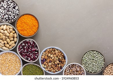 Different types of legumes in bowls, green and yellow peas, chickpeas and peanuts, colored beans and lentils, mung beans and beans, top view