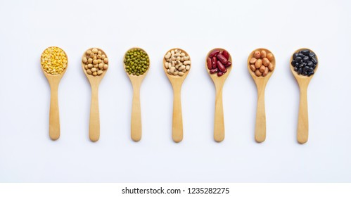 Different types of legumes on wooden spoon, white background.