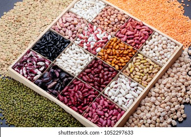 Different types of legumes. In wooden box.Varieties of beans.Small red bean,Scarlett runner bean Phaseolus coccineus ,butter bean,kidney bean,pinto and other sorts of beans.Top view.On dark stone