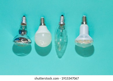 Different types of light bulbs on a blue background. Halogen, LED, incandescent lamp lies on the surface