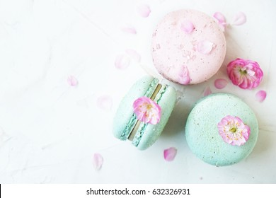 Different types of macaroons, french macaroons or macaron with spring sakura flowers. Colorful macaroons. Food background. Text space.