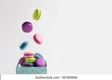 Different types of macaroons or macarons in motion falling (levitation) on background and in the box