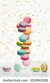 Different types of macaroons in motion falling on white background. Sweet and colourful french macaroons falling or flying in motion.
