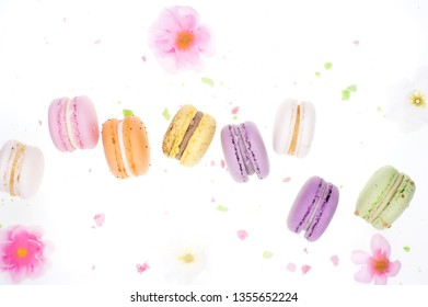 Different types of macaroons in motion falling on white background background. Sweet and colorful french macaroons falling or flying in motion