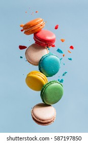 Different types of macaroons in motion falling on light  blue background. Sweet and colorful french macaroons falling or flying in motion.