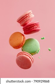 Different types of macaroons in motion falling on pink background. Sweet and colourful french macaroons falling or flying in motion.