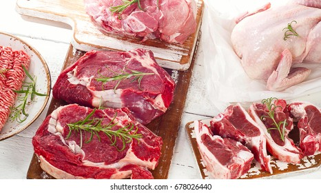 Different types of meat on a white wooden board