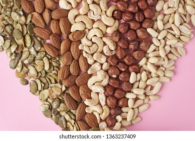Different types of nuts and pumpkin seeds on pink background, top view