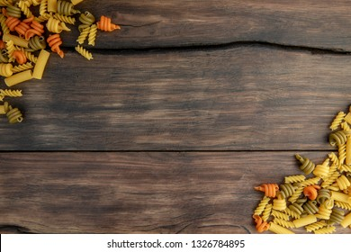 Different types of pasta on the wooden background. Top view, copy space