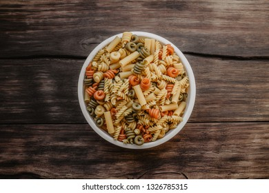Different types of pasta in plate on the wooden background. Top view