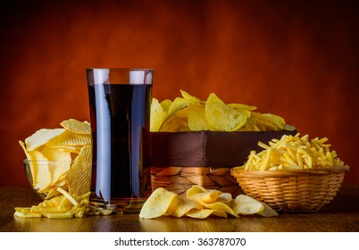 Different Types of Potato-snacks and glass of Cola, unhealthy food