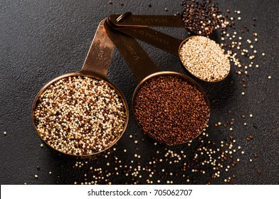 Different types of quinoa, white, red, black and mixed - South american grain - in metal measured spoons