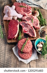 Different types of raw meat - beef, pork, lamb, chicken on a wooden board.