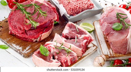 Different types of raw meat with fresh herbs.