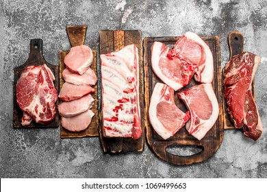 Different types of raw meat on the boards. On rustic background.