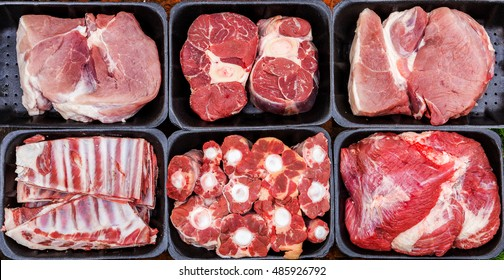 Different types of raw meat in plastic boxes, lamb shank on the bone, beef tail, beef neck, beef blade.