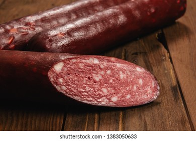 Different types of raw smoked sausage on a wooden background. Whole and cut stick