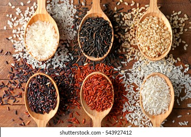 Different types of rice in spoons on wooden table, top view
