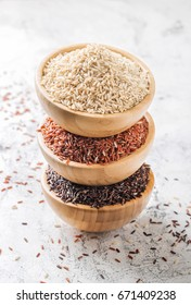 Different types of rice in a wooden bowls on white textured background