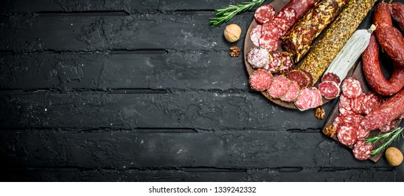 Different types of salami on wooden Board. On black rustic background.