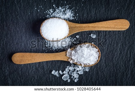 Different types of salt. Sea and kitchen salt. Top view on two wooden spoons on black background