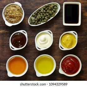 Different types of sauces and oils in bowls, top view
