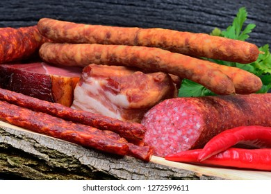 Different types of sausages with chili pepper and parsley on cutting board
