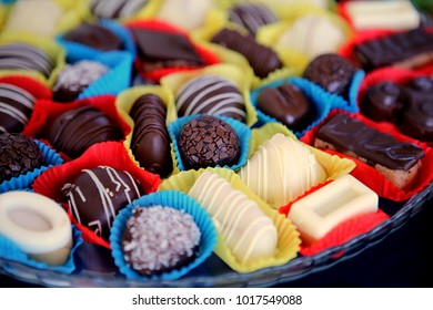 different types of small chocolate sweets placed in colorful paper mmm delicious