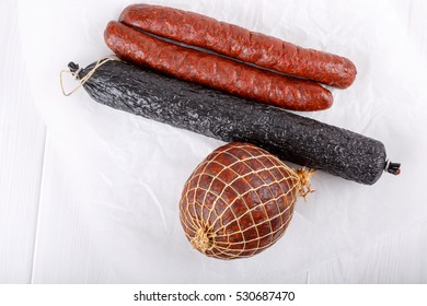 Different types of smoked salami sausages on white.