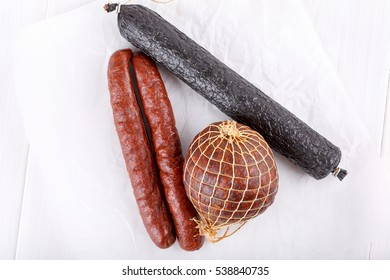 Different types of smoked salami sausages on white