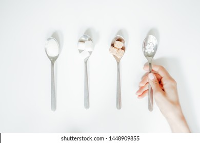 Different types of sugar, the hand holds a spoon with a sugar substitute