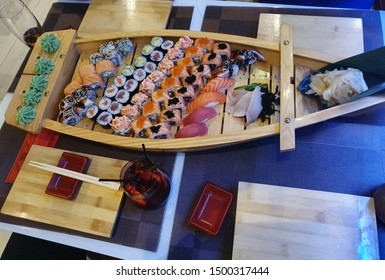 Different Types Of Sushi Food Served on a Wooden Boat at a Specific Restaurant, PHILADELPHIA Cheese,Red Dragon and Shrimp Volcano Sushi Rolls, Delicious Japanese Nigiri Dish with Raw Fish:Salmon,Tuna
