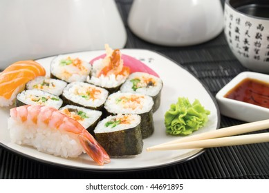 Different types of sushi in the plate with chopsticks and cup of tea