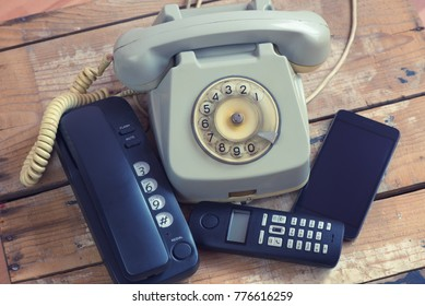 Different types of telephones on wooden board