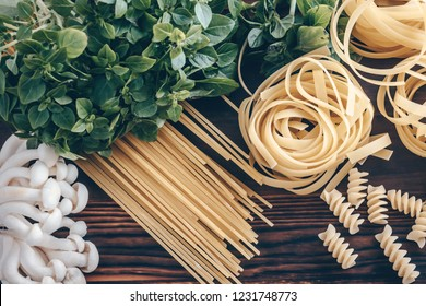 Different types of  uncooked pasta on wooden background. Fettuccine, spaghetti and fusilli with shimeji mushrooms and basil. Food background.