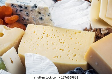 different types and varieties of cheese with grapes, nuts and dried apricots