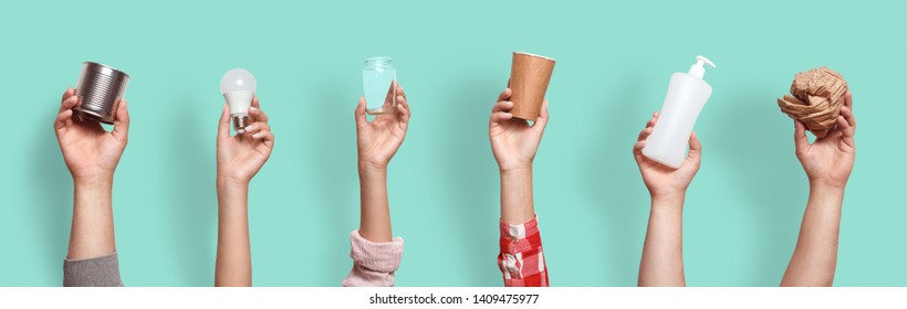 Different types of waste in the hands on a blue background. Sort garbage concept