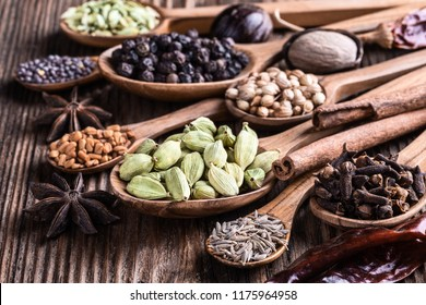 Different types of whole Indian spices in wooden spoons on rustic background close-up.  Black pepper, fenugreek, anise, cinnamon, cardamom, coriander, mustard, nutmeg, clove, cumin. Healthy food.