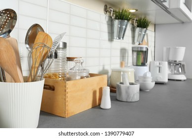 Different utensils and clean dishes on kitchen counter