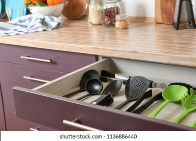 Different utensils for cooking in drawer on kitchen