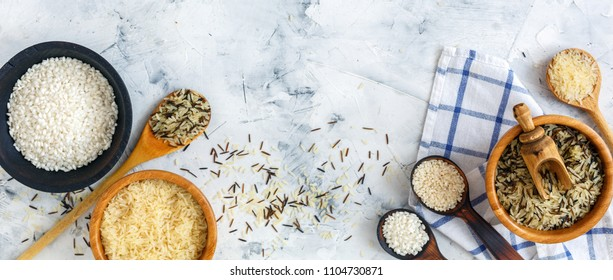 Different varieties of rice in wooden bowls and spoons on a white concrete background.