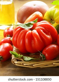 different varieties of tomato with basil on a wooden table