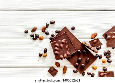 Different variety of chocolate and hazelnut on white wooden background top view space for text