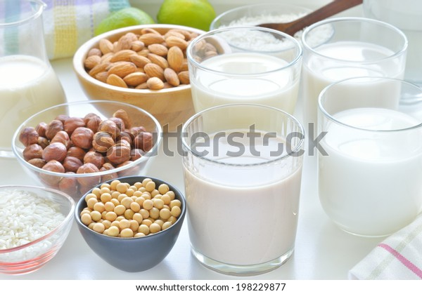 Different vegan milks on a table. Hazelnut, rice, soya and almond milk. Substitute for dairy milk.