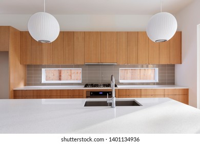 A different view of a modern kitchen featuring wooden cabinets