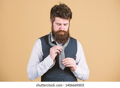 Different ways of tying necktie knots. Art of manliness. How to tie necktie. Start with your collar up and the tie around your neck. How to tie simple knot. Man bearded hipster try to make knot.