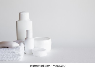 Different white beauty products on the gray background. Cares about people hair and body skin. Empty place for a text.
