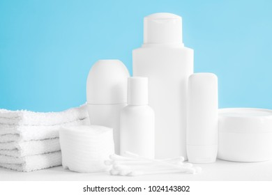 Different, white beauty toiletries, cotton wools and towels on blue background. Body relax and care products for women and men. Front view.