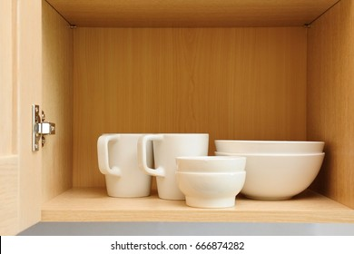 Different white dishes in cupboard in the kitchen